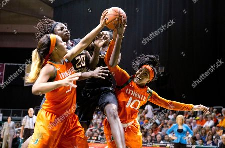 Miami's Erykah Davenport (30) and Michelle Woods (10) battle Florida State players Skakayla Thomas (20) and Adut Bulgak (2) for a loose ball during the second half of an NCAA basketball game in Coral Gables, Fla., . Florida State won 69-55