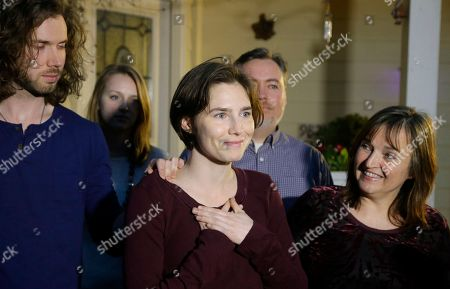 Amanda Knox, center, talks to reporters as her mother, Edda Mellas, right, and her boyfriend, Colin Sutherland, left, look on outside Mellas' home, in Seattle. Earlier in the day, Italy's highest court overturned the murder conviction against Knox and her ex-boyfriend over the 2007 slaying of Knox's roommate in Italy