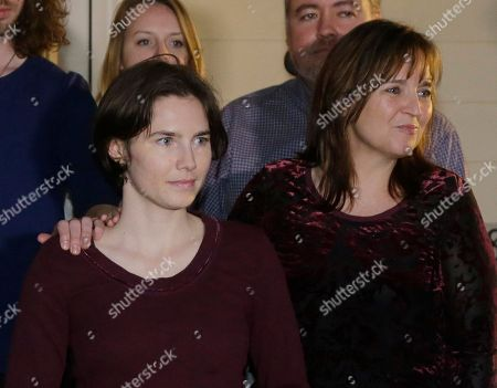 Amanda Knox, left, walks with her mother, Edda Mellas, right, to talk to the media outside Mellas' home, in Seattle. Italy's highest court overturned the murder conviction against Knox and her ex-boyfriend Friday over the 2007 slaying of Knox's roommate, bringing to a definitive end the high-profile case