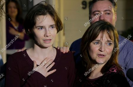 Amanda Knox, left, stands with her mother, Edda Mellas, right, as she talks to the media outside Mellas' home, in Seattle. Italy's highest court overturned the murder conviction against Knox and her ex-boyfriend Friday over the 2007 slaying of Knox's roommate, bringing to a definitive end the high-profile case that captivated trial-watchers on both sides of the Atlantic
