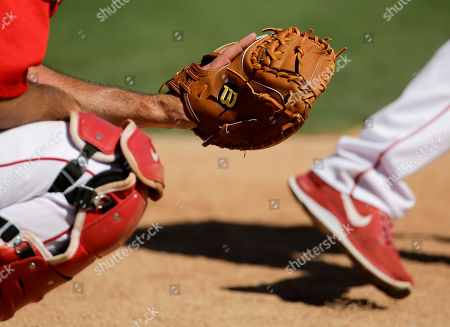 Los Angeles Angels catcher Drew Butera holds a Wilson catchers glove during batting practice a spring training baseball exhibition game Seattle Mariners in Tempe, Ariz., on . Hillerich & Bradsby Co., the company that made bats for a who's who of baseball greats, including Babe Ruth and Ted Williams, announced a deal Monday to sell its Louisville Slugger brand to rival Wilson Sporting Goods Co. for $70 million