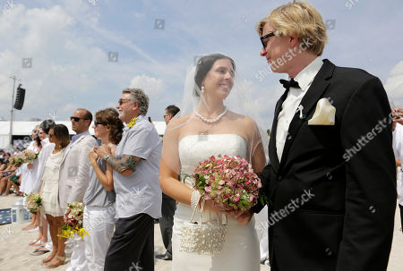 Gina Thomas, Jason Thomas Gina and Jason Thomas, of Naples, Fla., look at one another while being married during a group wedding and vow renewal as part of a weeklong Miami Beach Centennial celebration, in Miami Beach, Fla