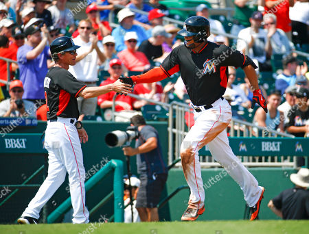 Giancarlo Stanton, Brett Butler Miami Marlins' Giancarlo Stanton is congratulated by third base coach Brett Butler (2) as he rounds third base after hitting a solo home run in the sixth inning of an exhibition spring training baseball game against the Washington Nationals, in Jupiter, Fla