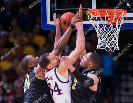 Shaquille Morris, Tekele Cotton, Perry Ellis Wichita State's Shaquille Morris, left, and Tekele Cotton, right, block Kansas' Perry Ellis (34) during the second half of an NCAA tournament college basketball game in the Round of 32 in Omaha, Neb