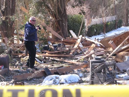 Fire investigator John Lightbody photographs the remains of a Stafford Township N.J. home, a day after the house was leveled by a natural gas explosion. Two of the 15 people injured in the blast remained in critical condition on Wednesday