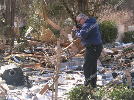 Stock Picture of Fire investigator John Lightbody photographs a damaged portable stove in the rubble of a Stafford Township N.J. home, a day after the house was leveled by a natural gas explosion. Two of the 15 people injured in the blast remained in critical condition on Wednesday