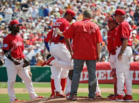 Odubel Herrera, Miguel Alfredo Gonzalez, Carlos Ruiz, Ryne Sandberg Philadelphia Phillies manager Ryne Sandberg, far right, joins Philadelphia catcher Carlos Ruiz (51), second baseman Odubel Herrera (37) and a trainer on the mound as they examine starting pitcher Miguel Alfredo Gonzalez (75) after Detroit Tigers Jose Iglesias's third-inning drive to the mound hit Gonzalez on the leg in a spring training baseball game in Clearwater, Fla., . Gonzalez was removed from the game. The Tigers went on to shut out the Phillies 6-0