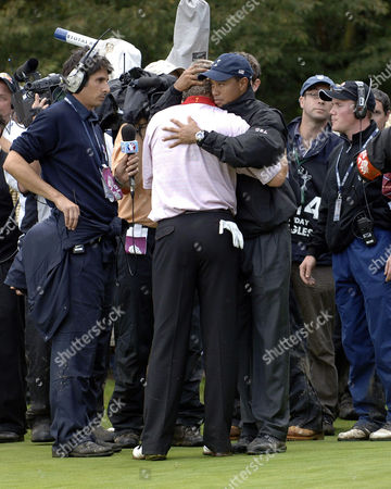 Darren Clarke embraces Tiger Woods on the 16th after closing out his match with Zack Johnson