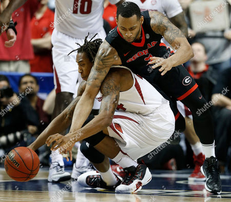 Arkansas guard Michael Qualls (24) and Georgia forward Marcus Thornton (2) vie for a loose ball during the first half of an NCAA college basketball game in the semifinal round of the Southeastern Conference tournament, in Nashville, Tenn