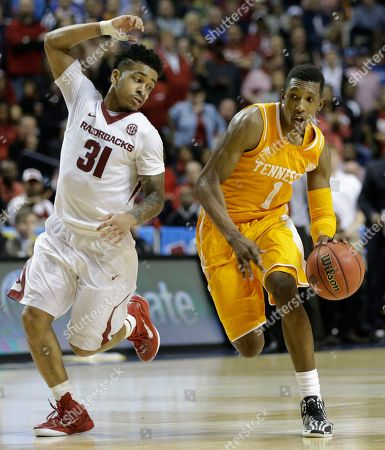 Stock Image of Tennessee guard Josh Richardson (1) moves by Arkansas guard Anton Beard (31) during the second half of an NCAA college basketball game in the quarterfinal round of the Southeastern Conference tournament, in Nashville, Tenn. Arkansas won 80-72
