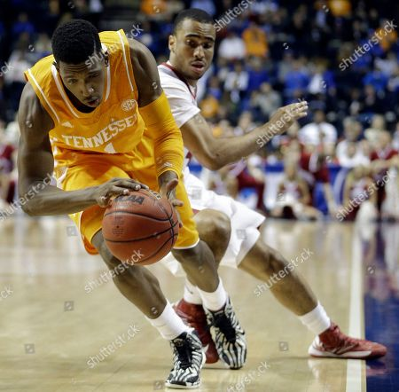 Tennessee guard Josh Richardson (1) moves the ball as Arkansas guard Jabril Durham (4) defends during the first half of an NCAA college basketball game in the quarterfinal round of the Southeastern Conference tournament, in Nashville, Tenn