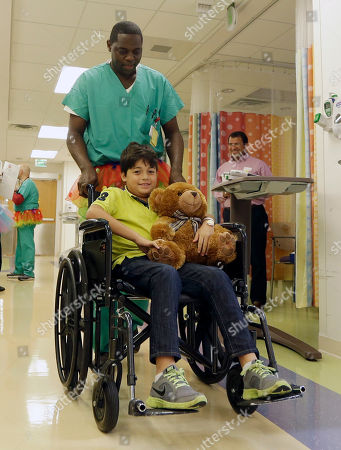 Operating room assistant Tony Smith wheels patient Jose Gabriel Matamoros 10-years-old, of Weston, at Joe DiMaggio Children's Hospital in Hollywood, Fla. One morning last summer, Smith slipped a colorful tutu over his scrubs in the pre-op ward of a South Florida hospital to grant the wish of a young patient heading to surgery, within weeks Tutu Tuesday was born