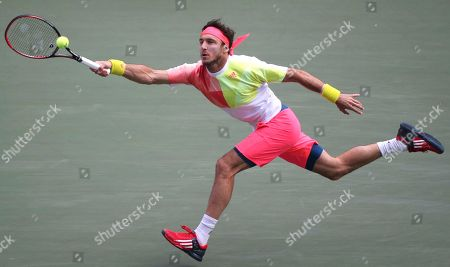 Juan Monaco of Argentina returns a shot against Croatia's Marin Cilic during the quarterfinal match of Japan Open tennis championships in Tokyo