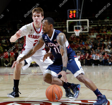 Stock Image of Ryan Boatright, Robert Cartwright Connecticut guard Ryan Boatright (11) dribbles past Stanford guard Robert Cartwright during the first half on an NCAA college basketball game, in Stanford, Calif