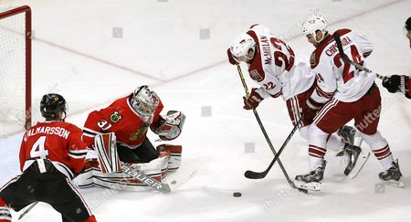 Niklas Hjalmarsson, Antti Raanta, Kyle Chipchura, Brandon McMillan Arizona Coyotes center Kyle Chipchura (24) steps on the stick of Brandon McMillan (22) keeping him from getting a shot on Chicago Blackhakws goalie Antti Raanta (31) as Niklas Hjalmarsson (4) watches, during the second period of an NHL hockey game, in Chicago