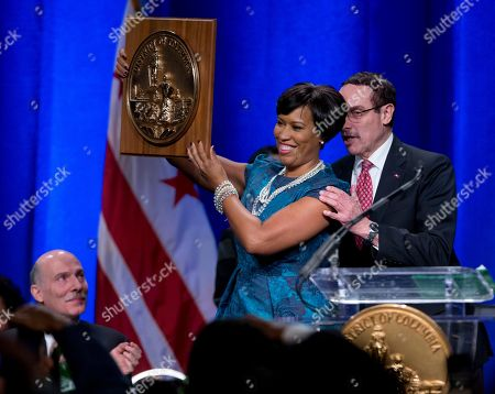 Vincent Gray, Muriel Bowser, Phil Mendelson Washington Mayor Muriel Bowser holds the seal of the District of Columbia after accepting it from former Mayor Vincent Gray, right, as council chairman Phil Mendelson watches at left, during the District of Columbia Mayoral Inauguration ceremony at the Convention Center in Washington