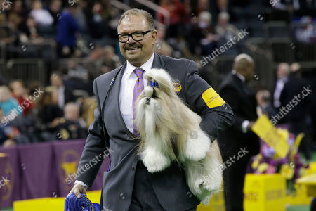 Luke Ehricht carries Rocket, a shih tzu co-owned Patty Hearst after it won the toy group competition at the Westminster Kennel Club dog show, at Madison Square Garden in New York