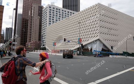 This photo pedestrians walk past the construction site of the Broad Museum in downtown Los Angeles. The new contemporary art museum that will be free to visitors, is set to open Sept. 20. Museum officials on Thursday, Feb. 5, 2015 announced the opening date for the block-long, three-story building next door to the Walt Disney Concert Hall. The $140 million institution will showcase the priceless collection of billionaire philanthropist Eli Broad. Among the artists whose work will be displayed are Andy Warhol, Jasper Johns, Ed Ruscha, Cindy Sherman, and Roy Lichtenstein