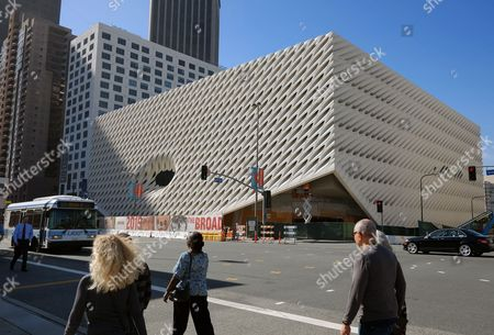Pedestrians walk past the construction site of the Broad Museum on in downtown Los Angeles. The new contemporary art museum that will be free to visitors, is set to open Sept. 20. Museum officials on Thursday, Feb. 5, 2015 announced the opening date for the block-long, three-story building next door to the Walt Disney Concert Hall. The $140 million institution will showcase the priceless collection of billionaire philanthropist Eli Broad. Among the artists whose work will be displayed are Andy Warhol, Jasper Johns, Ed Ruscha, Cindy Sherman, and Roy Lichtenstein