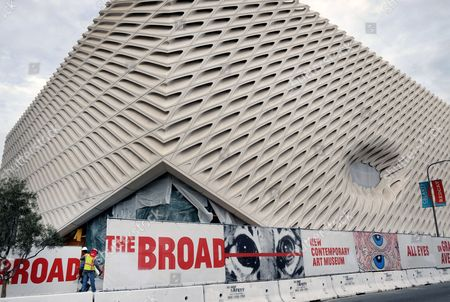 Workers walk onto the construction site of the Broad Museum in downtown Los Angeles. The new contemporary art museum that will be free to visitors, is set to open Sept. 20. Museum officials on Thursday, Feb. 5, 2015 announced the opening date for the block-long, three-story building next door to the Walt Disney Concert Hall. The $140 million institution will showcase the priceless collection of billionaire philanthropist Eli Broad. Among the artists whose work will be displayed are Andy Warhol, Jasper Johns, Ed Ruscha, Cindy Sherman, and Roy Lichtenstein