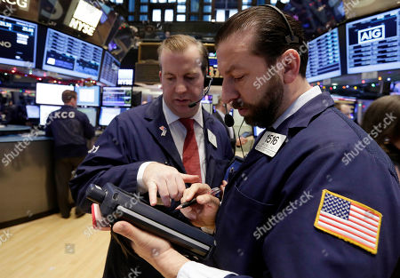 James Doherty, Greg Mulligan Traders James Doherty, left, and Greg Mulligan, work on the floor of the New York Stock Exchange . US stocks opened lower Monday, led by declines in energy stocks as the price of oil plunged again