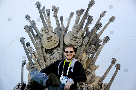 Stock Picture of Jason Wright Jason Wright poses for photos in a chair made with guitars at the Gibson booth at the International CES, in Las Vegas