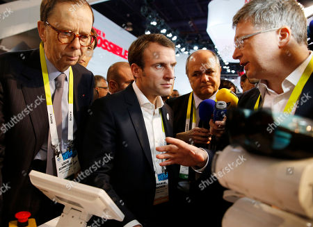 Stock Picture of Emmanuel Macron, Henri Seydoux, Louis Schweitzer French finance minister Emmanuel Macron, center, tours the Parrot booth with Parrot CEO and founder Henri Seydoux, right, and Louis Schweitzer, left, at the International CES in Las Vegas