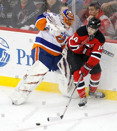 Adam Henrique, Jaroslav Halak New Jersey Devils center Adam Henrique, right, makes a pass to center Scott Gomez as New York Islanders goalie Jaroslav Halak, left, of Slovakia, leaves his net during the third period of an NHL hockey game, in Newark, N.J. Gomez scored on the pass