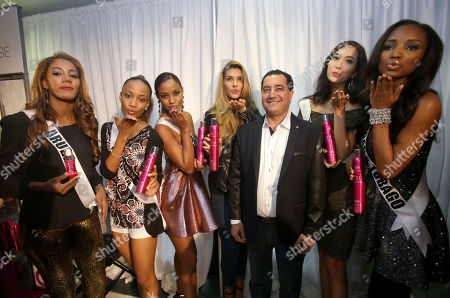 Stock Image of Farouk Shami, Digene Zimmerman, Roxanne Didier-Nicholas, Laurien Angelista, Camille Cerf, Pimbongkod Chankaew, Jevon King Miss Universe contestants pose or photos with hairstylist and founder of the haircare brand CHI, Farouk Shami, third from left, during a break in rehearsals, at Florida International University in Miami. Contestants from left: Digene Zimmerman of Aruba, Roxanne Didier-Nicholas of St. Lucia, Laurien Angelista of Curacao, Camille Cerf of France, Pimbongkod Chankaew of Thailand, and Jevon King of Trinidad and Tobago. The Miss Universe pageant will be held Jan. 25, in Miami