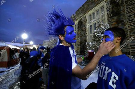 Nick Stevenson, left, paints Jordan Bollmann's face outside of Cameron Indoor Stadium prior to Duke's basketball game against North Carolina in Durham, N.C