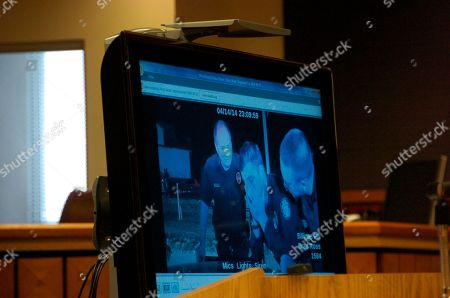 Police video footage of the April 2014 shooting of Richard Ramirez by Billings Police Officer Grant Morrison, center in screen, is shown to a seven-person jury in Billings, Mont. on . The unarmed man killed by the police officer during a traffic stop was told repeatedly to raise his hands before the officer shot him three times, according to video footage. The jury will decide if the shooting was justified as part of a mandatory inquest into the shooting
