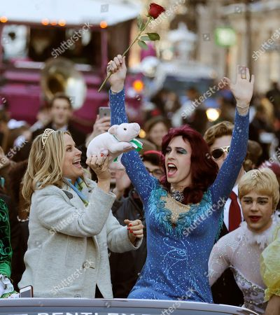 """Amy Poehler Actress Amy Poehler, left, holds up a stuffed animal pig as Sam Clark, dressed in drag, cheers as she rides in a convertible through Harvard Square in Cambridge, Mass., . Poehler was honored as """"Woman of the Year"""" by the Hasty Pudding Theatricals at Harvard University"""
