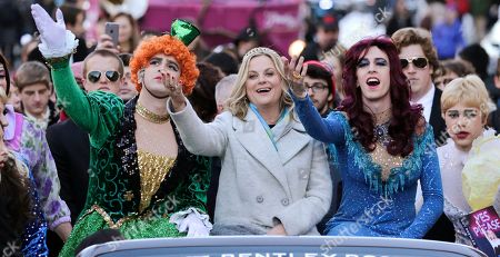 """Amy Poehler Actress Amy Poehler, center, waves as she is seated with Jason Hellerstein, left, and Sam Clark, who are dressed in drag, while riding in a convertible through Harvard Square in Cambridge, Mass., . Poehler was honored as """"Woman of the Year"""" by the Hasty Pudding Theatricals at Harvard University"""