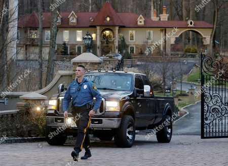 "A police officer walks near a truck carrying children from the home of Teresa Giudice, a cast member of Bravo's ""Real Housewives of New Jersey,"" and her husband Giuseppe ""Joe"" Giudice, in the Towaco section of Montville Township, N.J. Teresa Giudice is scheduled to report to a federal prison in Danbury, Connecticut, on Monday morning to begin serving a 15-month sentence for bankruptcy fraud. U.S. District Judge Esther Salas staggered her sentence with her husband's so they wouldn't be in prison at the same time and unable to care for their four daughters. She and her husband pleaded guilty last year and admitted hiding assets from bankruptcy creditors and submitting phony loan applications to get some $5 million in mortgages and construction loans"