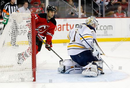 Jhonas Enroth, Scott Gomez Buffalo Sabres goalie Jhonas Enroth, right, of Sweden, makes a save on a shot by the New Jersey Devils during the second period of an NHL hockey game, in Newark, N.J. Devils' Scott Gomez attacks on the play