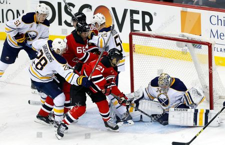 Michal Neuvirth, Scott Gomez Buffalo Sabres goalie Michal Neuvirth (34), of the Czech Republic, blocks a shot by New Jersey Devils center Scott Gomez (21) during the third period of an NHL hockey game, in Newark, N.J. The Devils won 2-1 in a shootout
