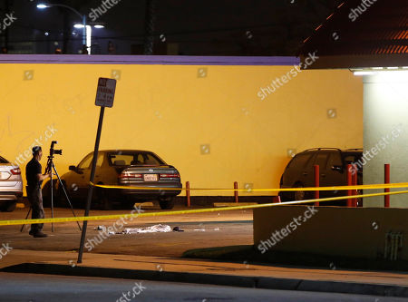 "A Los Angeles County Sheriff's Department investigator photographs the scene of an accident at a parking lot in Compton, Calif., . A lawyer for Marion ""Suge"" Knight, a Death Row Records founder, says Knight was driving a car involved in an accident"