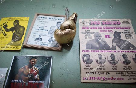 Stock Image of Deontay Wilder A golden glove signed by Hall of Fame American boxer Virgil Hill hangs on the wall of Skyy Boxing Gym next to posters of other boxers including the WBC heavyweight champion Deontay Wilder, in Northport, Ala. Wilder has gone from driving a beer delivery truck to tooling around in a Hummer, among other sporty cars, and gets to watch the Super Bowl from the stands not his living room