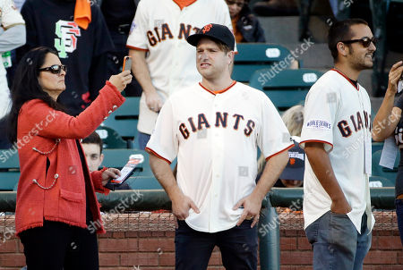 Robin Williams' former wife Marsha Garces takes pictures of his sons Zak and Zelda Williams before Game 5 of baseball's World Series between the Kansas City Royals and the San Francisco Giants, in San Francisco