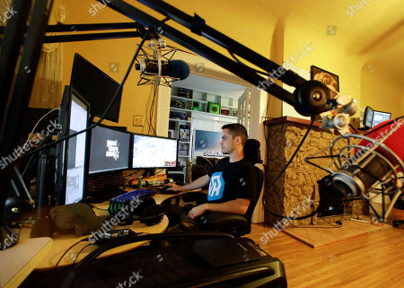 Adam Young views multiple computer screens where he plays video games for a living, in Lakeland, Fla. Young is one of three roommates that plays the games online to entertain others