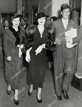 Stock Photo of Gloria Morgan Vanderbilt, Gloria Vanderbilt, Laura Morgan, Laura Consuelo Morgan, Mrs. Benjamin Thaw, Tamar, Oliver Gardner Gloria Morgan Vanderbilt, center, smiles as she leaves the Supreme Court in New York with her sister Laura Thaw, and her secretary Oliver Gardner in this undated photo. Mrs. Vanderbilt was apparently quite pleased with the results of the secret trial in her fight for custody of her daughter, Gloria Vanderbilt