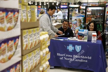 Blue Bridge Benefits LLC agent Patricia Sarabia, right, and Adolfo Briceno, left, with Spanish Speaking LLC, help a potential customer with Blue Cross Blue Shield at a kiosk promoting Obama Care at Compare Foods in Winston-Salem, N.C. Such atypical approaches to selling health insurance policies are playing out across the country since the second round of open enrollment under the federal Affordable Care Act opened in mid-November. Insurance companies and some states are focusing heavily on signing up eligible Hispanics, a group that accounts for a large share of the nation's uninsured but largely avoided applying for coverage during the first full year the health care reform law was in effect. Hispanics accounted for just 11 percent of those who enrolled in the private policies sold during the initial sign-up period, which ended in March