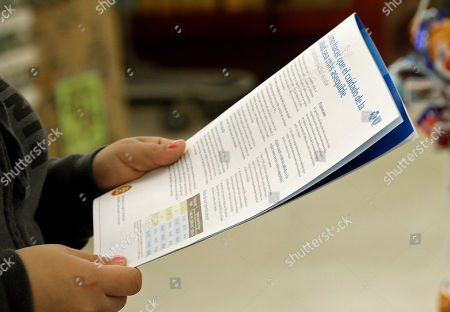 A customer reads information in Spanish about Blue Cross Blue Shield and Obama Care at a kiosk at Compare Foods in Winston-Salem, N.C. Such atypical approaches to selling health insurance policies are playing out across the country since the second round of open enrollment under the federal Affordable Care Act opened in mid-November. Insurance companies and some states are focusing heavily on signing up eligible Hispanics, a group that accounts for a large share of the nation's uninsured but largely avoided applying for coverage during the first full year the health care reform law was in effect. Hispanics accounted for just 11 percent of those who enrolled in the private policies sold during the initial sign-up period, which ended in March