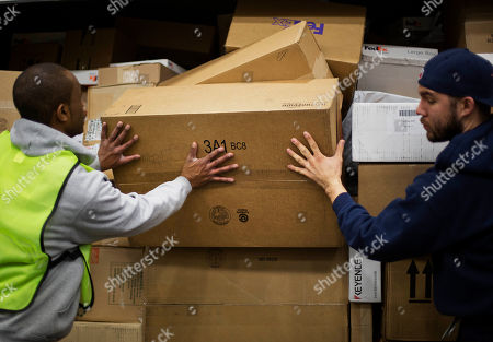 Randy Reese, Aaron Gilbert Handlers Randy Reese, left, and Aaron Gilbert, stop packages from falling out of an airline container as they're sorted before being loaded onto trucks for delivery at a FedEx facility, in Marietta, Ga. With just ten days until Christmas, the delivery service is expecting a spike of packages as customers rush to get deliveries before the holiday