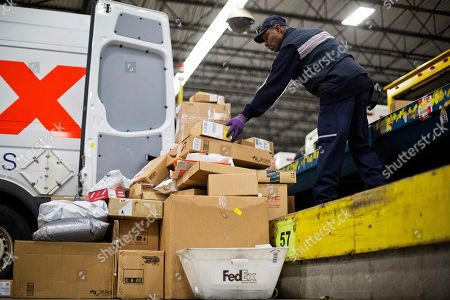 Thomas Williams Courier Thomas Williams adds a box to a pile of packages to be loaded onto a truck for delivery at a FedEx facility, in Marietta, Ga. The Memphis-based shipping company says it expects to handle 22.6 million packages on Monday, its busiest day of the year