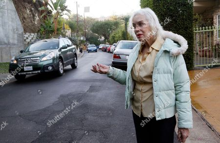 """Stock Image of In t photo resident Paula Hamilton stands on a street outside her house in the Sherman Oaks section of Los Angeles. """"The traffic is unbearable now. You can't even walk your dog,"""" said Hamilton, who lives on a once quiet little street. When the people whose houses hug the narrow warren of streets paralleling the busiest urban freeway in America began to see bumper-to-bumper traffic rushing by their homes a year or so ago they were baffled. When word spread that the explosively popular new smartphone app Waze was sending many of those cars through their neighborhood in a quest to shave five minutes off a daily rush-hour commute, they were angry and ready to fight back"""