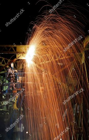 Stock Photo of Sparks cascade as workers use a welding torch to cut through steel trusses on the old Clair - Fort Kent Bridge that spans the the Saint John River between Clair, New Brunswick, Canada and Fort Kent, Maine, . The 84-year-old bridge is being dismantled. A new bridge at the border crossing opened in July