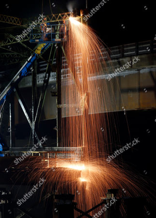 Sparks cascade like a waterfall as workers use a welding torch to cut through steel trusses on the old Clair - Fort Kent Bridge that spans the the Saint John River between Clair, New Brunswick, Canada and Fort Kent, Maine, . The 84-year-old bridge is being dismantled. A new bridge at the border crossing opened in July