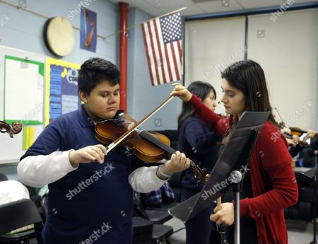 Music teacher Maria Pulido, right, works with Brian Gonzalez on his violin at the Richard Edwards Elementary School, in Chicago. Chicago now joins dozens of schools districts across the country that teach mariachi music in schools. It's a way to connect schools and parents from Hispanic communities, say organizers