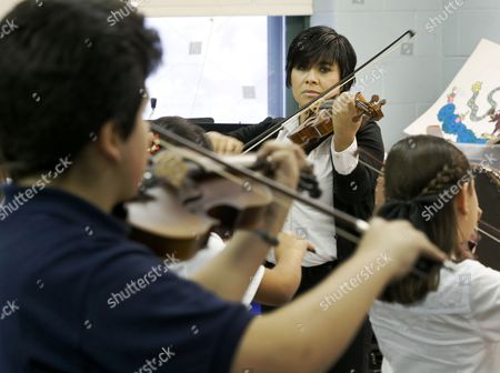 Music teacher Elizabeth Rodriguez watches over as students perform mariachi music at the Richard Edwards Elementary School, in Chicago. Chicago now joins dozens of schools districts across the country in cities like Las Vegas, San Antonio and Tucson, Ariz., that teach mariachi music in schools. It's a way to connect schools and parents, many who speak Spanish, from Hispanic communities says organizers